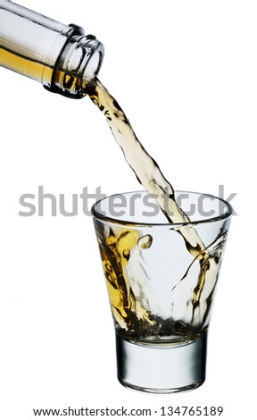 Whiskey being poured into a glass isolated on white