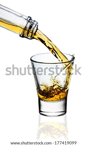 Whiskey being poured into a glass isolated on white - stock photo