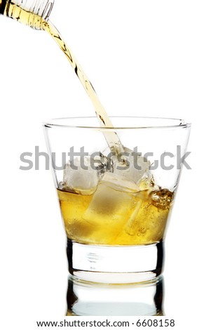 Whiskey being poured into a glass (isolated on white background) - stock photo