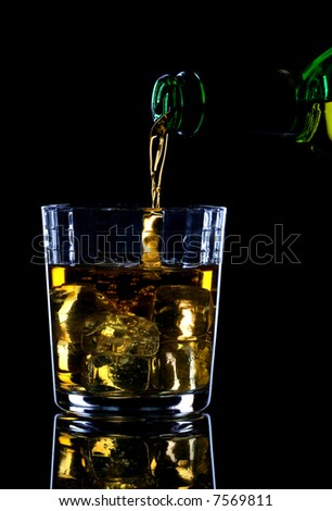Whiskey being poured into a glass of ice against a black background. - stock photo
