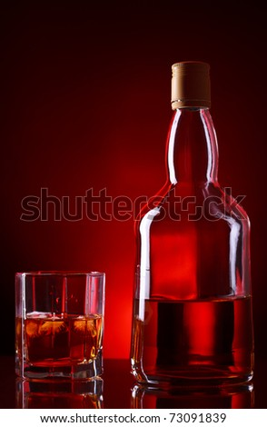whiskey bottle and glass on red background