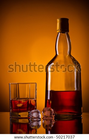 whiskey bottle, ice and glass, orange background - stock photo