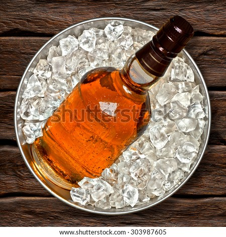 Whiskey bottle in ice bucket top view on wooden background including clipping path - stock photo