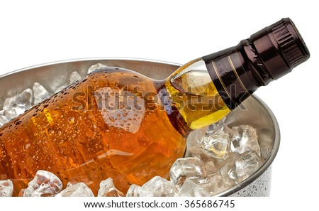 Whiskey bottle in ice bucket with crushed ice on white background