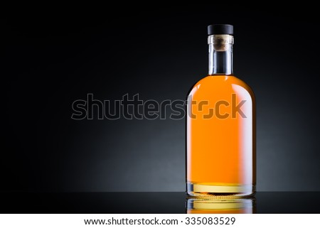 Whiskey bottle on black glass surface - stock photo