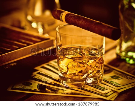 Whiskey, cigar and money on a table, toned image - stock photo