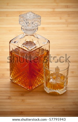 Whiskey decanter and drink with ice - stock photo