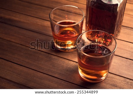 Whiskey drinks on wood table. Alcohol background. - stock photo