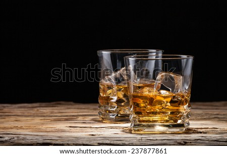 Whiskey drinks on wood with ice cubes - stock photo