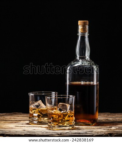 Whiskey drinks with bottle on wood - stock photo