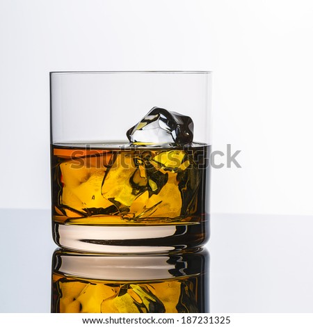 whiskey glass alcohol with ice cubes rocks with reflection drink