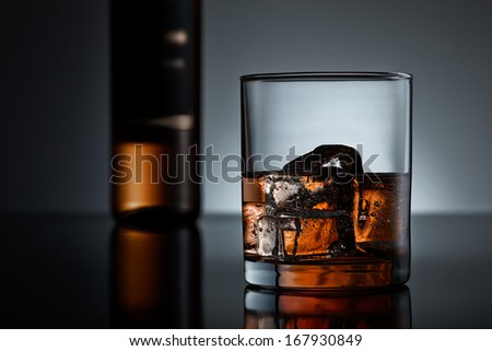 Whiskey glass and bottle arrangement on black surface - stock photo