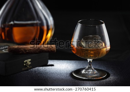 Whiskey glass/ cognac glass, whiskey bottle and cigar on the background - stock photo