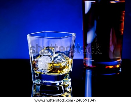 whiskey glass near bottle on light tint blue disco on black table with reflection - stock photo