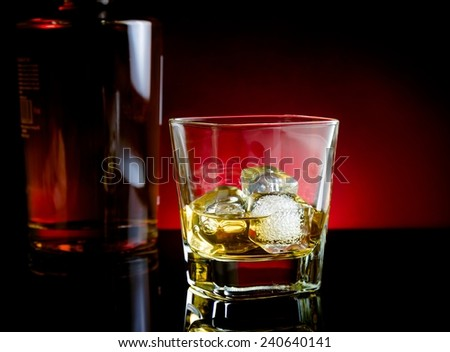 whiskey glass near bottle on light tint red disco on black table with reflection - stock photo