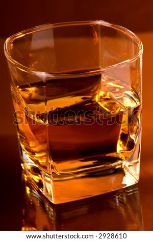 Whiskey , glass of whiskey placed on glass surface. Low intense warm color background light.