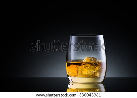 Whiskey glass on black glass surface - stock photo