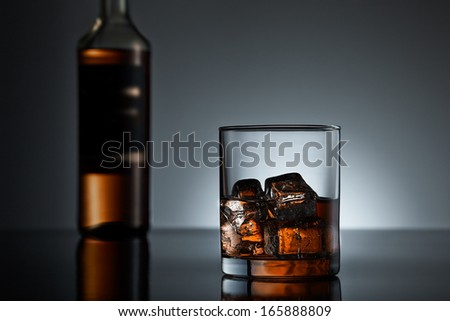 Whiskey glass with a bottle in background on black surface - stock photo