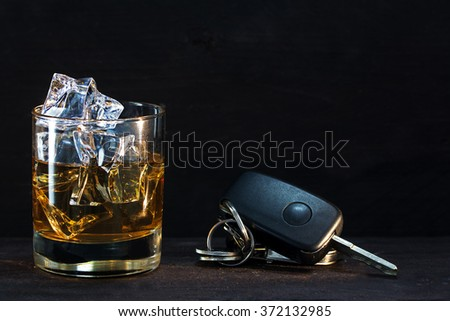 Whiskey glass with ice and car keys on a rustic wooden table, dark background with copy space, concept alcohol and driving - stock photo