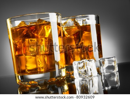 Whiskey glass with ice cubes - stock photo