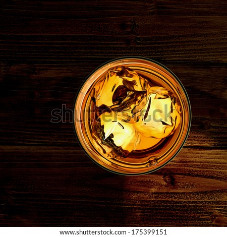 Whiskey glass with ice cubes from top on wooden background with copyspace - stock photo
