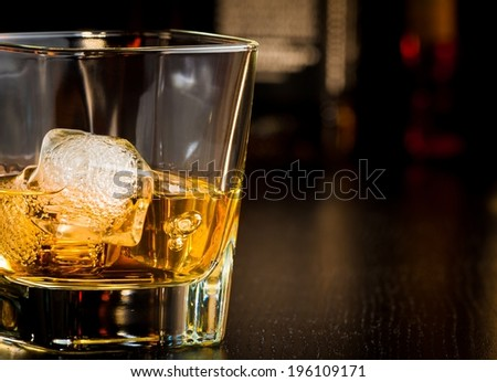 whiskey glass with ice in front of bottles on wood table with space for text - stock photo