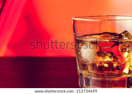 whiskey glass with ice on bar table lounge bar atmosphere with space for text - stock photo