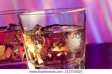 whiskey glass with ice on bar table on warm atmosphere lounge bar concept