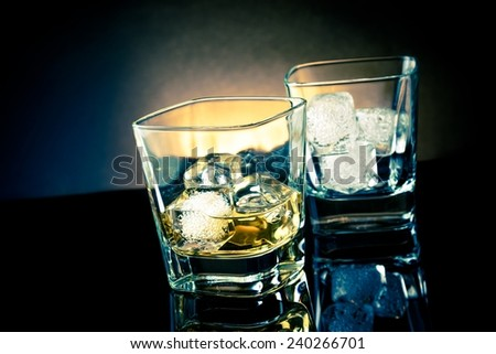 whiskey glasses with ice and light tint blue disco on black background, with reflection - stock photo