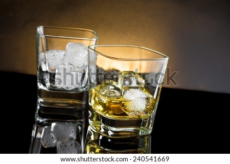 whiskey glasses with ice and warm light on black background, with reflection - stock photo