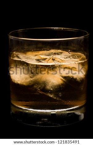 whiskey in a glass with ice backlit and isolated on a black background - stock photo