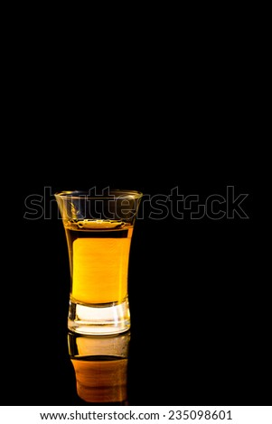 Whiskey in a shot glass isolated on black background - stock photo