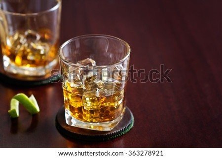 whiskey in glass on wooden background, blank text - stock photo