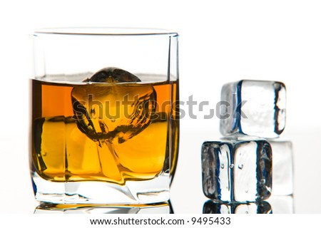 Whiskey in glass with ice cubes - stock photo
