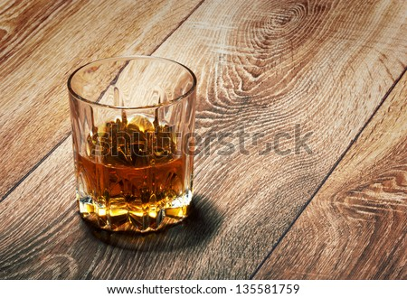 whiskey in glasses on wooden table - stock photo