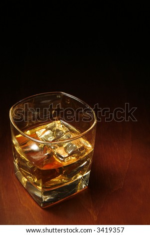 Whiskey in light pool on brown table with copyspace - stock photo
