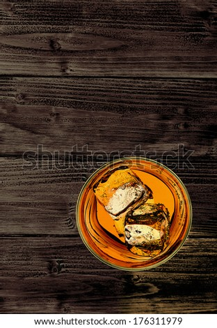 Whiskey in rocks glass with ice cubes on wooden background
