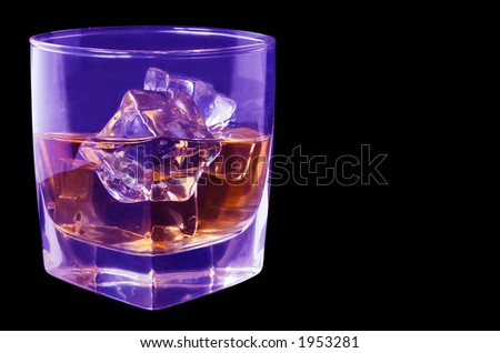 Whiskey in tumbler under ultra-violet light with black background - stock photo
