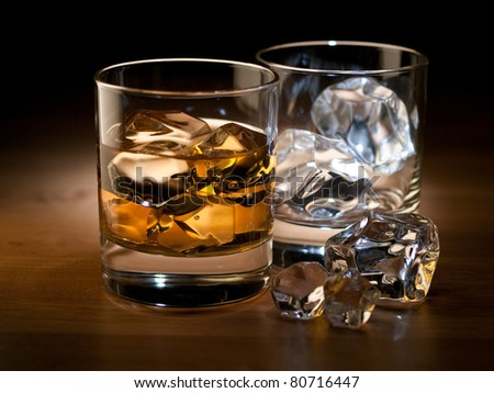 whiskey on the rocks and an empty glass with ice cubes - stock photo
