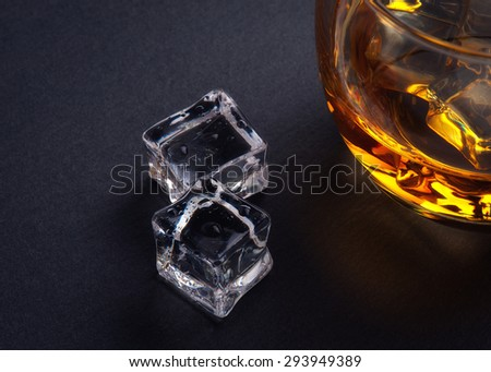 Whiskey on the rocks in a glass tumbler standing on a bar counter in the shadows with a highlight over copyspace or a place for product placement - stock photo