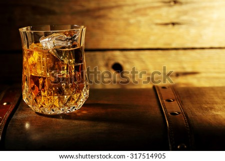 whiskey on the rocks on an old chest against wooden surface - stock photo