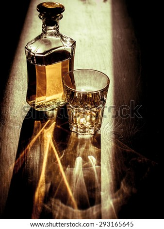 Whiskey on the rocks with back light and strong reflections - stock photo