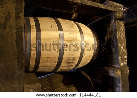 Whiskey or bourbon barrels aging in old distillery warehouse - stock photo