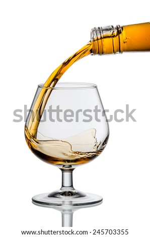 whiskey or brandy being poured into a glass - stock photo