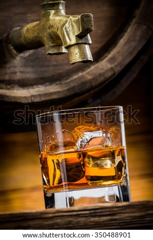 whiskey or brandy is poured into a glass from oak barrel