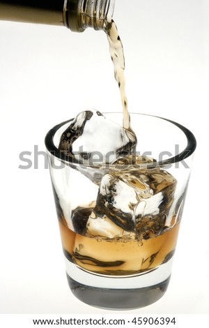 Whiskey poured on the rocks in an empty old fashioned glass on a white background - stock photo