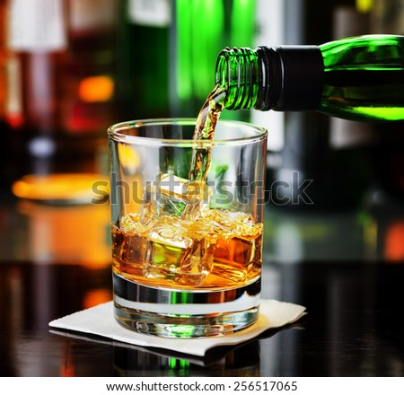 Whiskey pouring from a bottle into a glass in a bar. Scotch and Irish Single Malt or Blended Whiskey. - stock photo