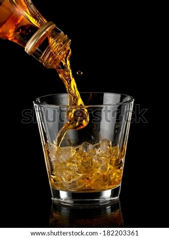 Whiskey pouring in a glass with ice - stock photo