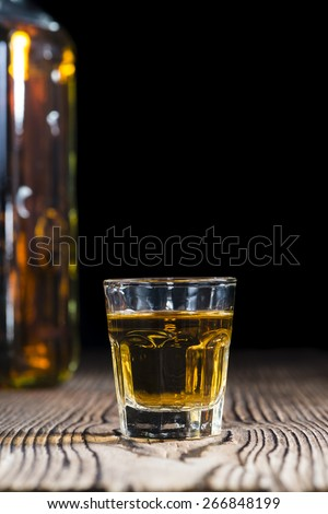 Whiskey Shot (close-up shot) on rustic wooden background - stock photo