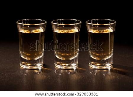 Whiskey shots in the dark - stock photo